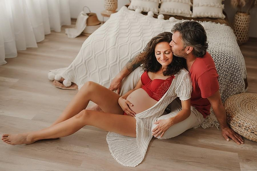 Das Bild zeigt ein glückliches Pärchen bei einem Schwangerschafts-Fotoshooting in einem gemütlich eingerichteten Fotostudio in München.