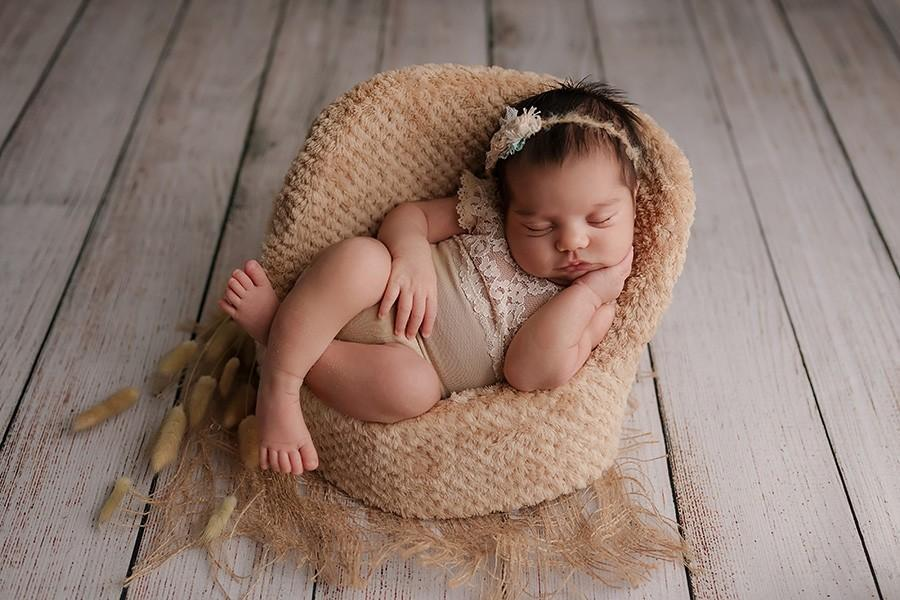 Das Babyfoto zeigt ein kleines schlafendes Neugeborenes im Boho-Stil gekleidet auf einem kleinen Sessel und wurde von der Babyfotografin Lucky Memory in München aufgenommen
