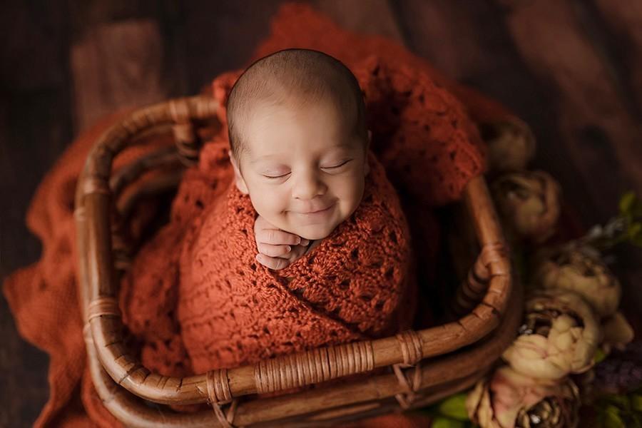 Neugeborenes mit süßen Lachen beim Babyshooting in Herbst Farben